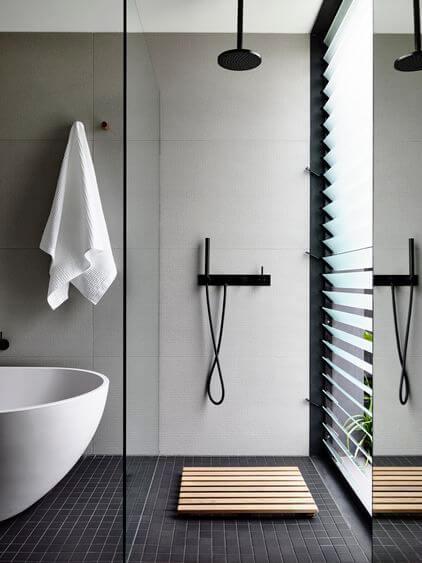 Badeværelse med badekar og moderne bruseniche.