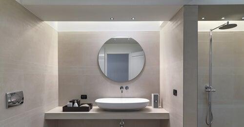 Rundt spejl med lys over håndvask.