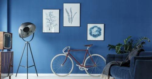 Mat blå malet væg med malerier og cykel