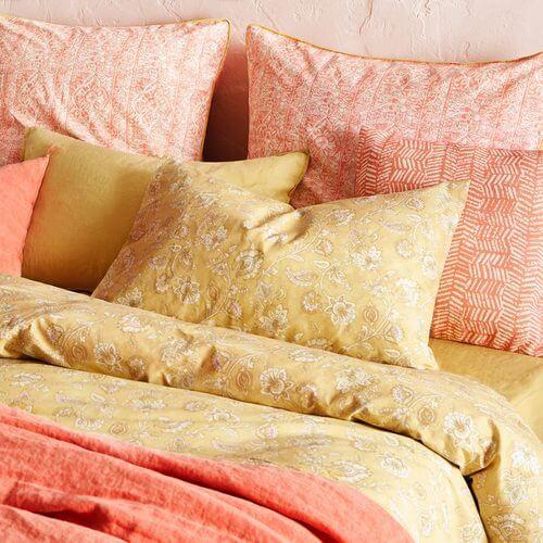 Sengetøj i gule og orange nuancer.