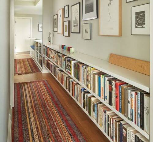 Lang gang indrettet med bøger og billedrammer.