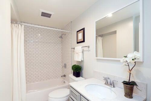 Hvidt badeværelse med stort spejl og badekar.