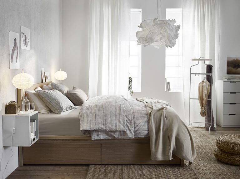 Seng der står i et lyst soveværelse