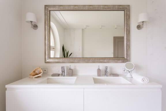 Stort spejl på lyst badeværelse.
