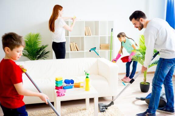 Familie gør rent i stuen sammen. Mor tørrer hylder af, far og søn støvsuger.