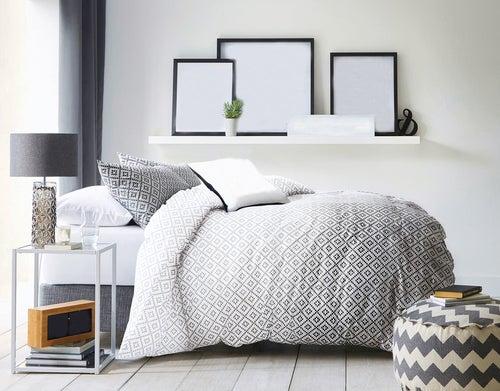 Lyst soveværelse med sort-hvidt sengetæppe.