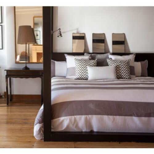 Soveværelse med lilla-stribet sengebetræk.