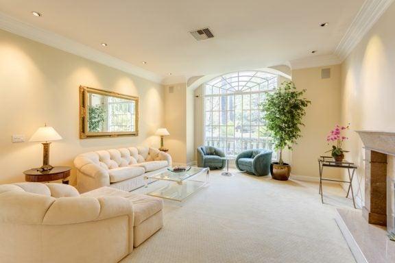 Creme stue med stort vindue og spejl på væggen.