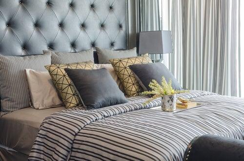 Seng med stribet sengetæppe og forskellige puder.