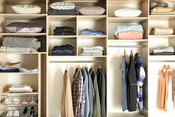 Hylder med tøj i walk-in closet.