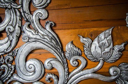 Dekoration i sølv på træmøbel.