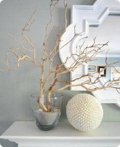 En gren i et glas med sand giver et enkelt og elegant udtryk