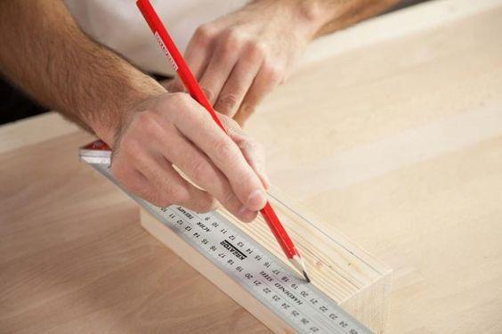 Mand måler op for at bore i forskellige materialer