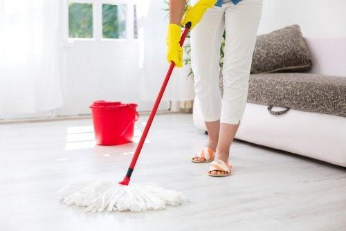 En kvinder mopper gulvet for at rengøre dit hjem