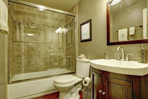 En brusekabine i glas på et lille badeværelse
