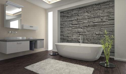 En smuk, grå stenvæg på badeværelset ved badekarret