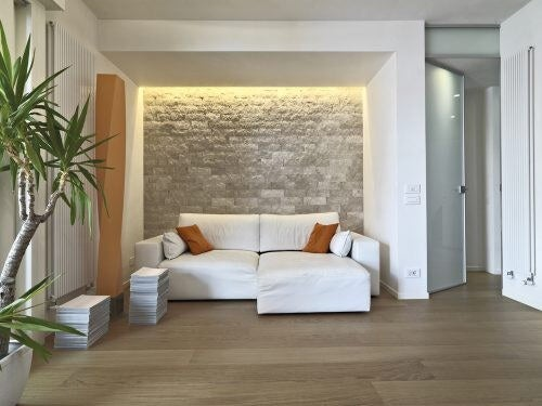 En smuk stenvæg bag sofaen i stuen