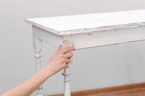 Person sliber sit træmøbel med sandpapir