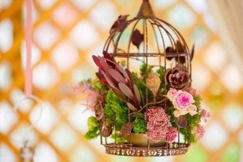 arrangering af blomster i et fuglebur