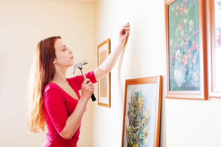 kvinde er er ved at hænge malerier op