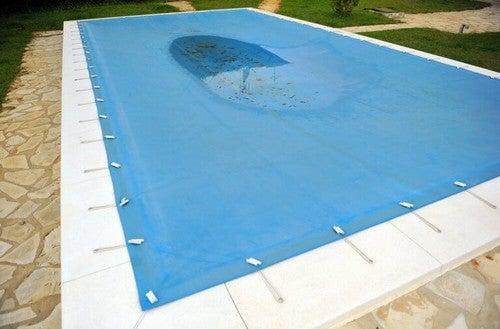 En presenning beskytter poolen mod blade og snavs