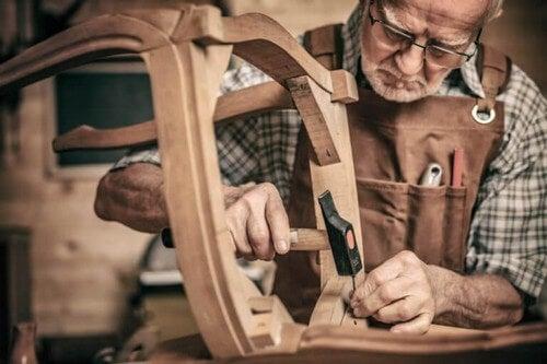 Mand reparerer en gammel stol
