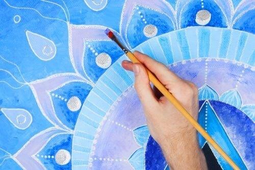 Person maler blå mandala