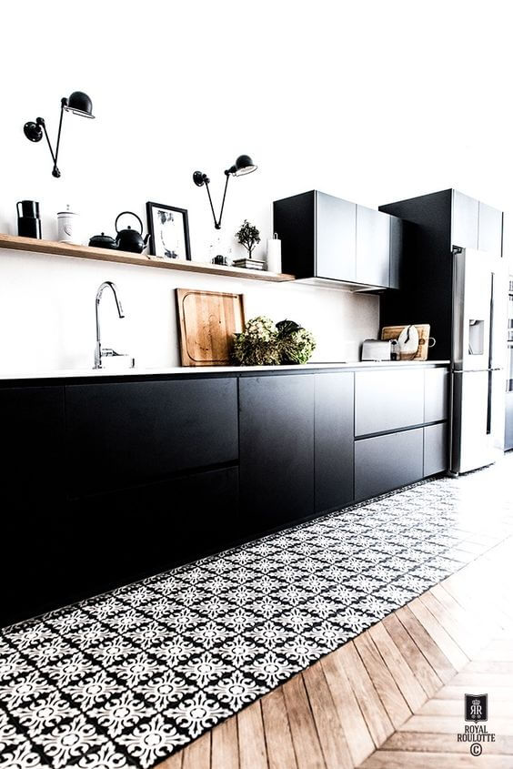 sort køkken med fliser og trægulv