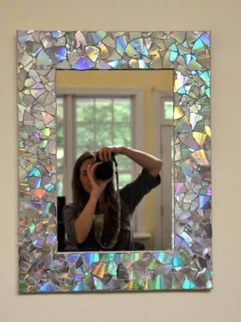 eksempel på hvordan du kan dekorere dine spejle med gamle cder. her ses en ramme lavet af cd-stykker