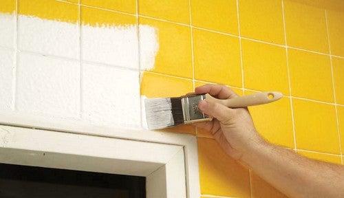 Person maler fliserne gule