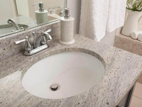 Et badeværelse med bordplade af granit.