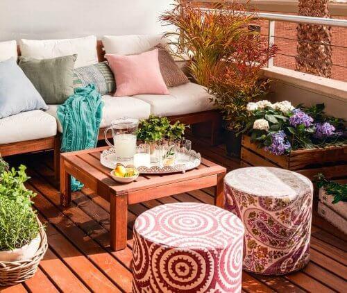 En lille terrasse dekoreret med møbler og planter.