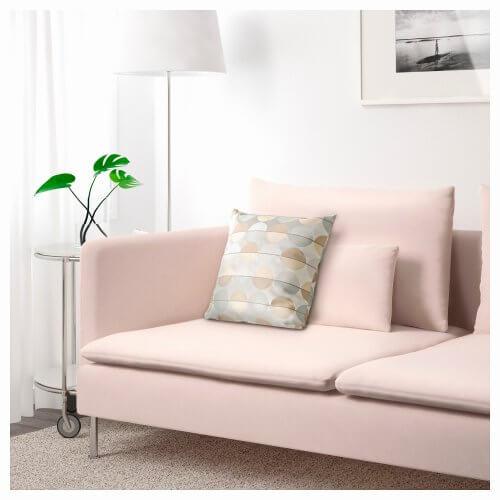 En lys rosa sofa i en stue.
