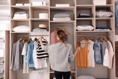 Et rent hjem: En kvinde lægger sit tøj på plads i sit skab.