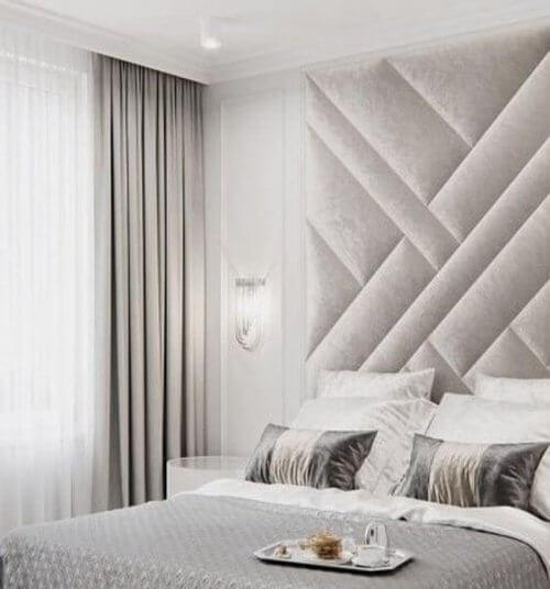 En soveværelsesvæg dekoreret med stof.