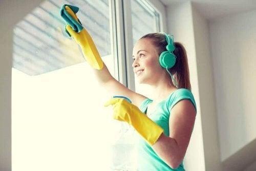 Kvinde er i gang med at pudse vinduer