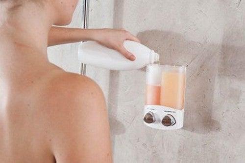 Kvinde fylder væghængt dispenser op med sæbe