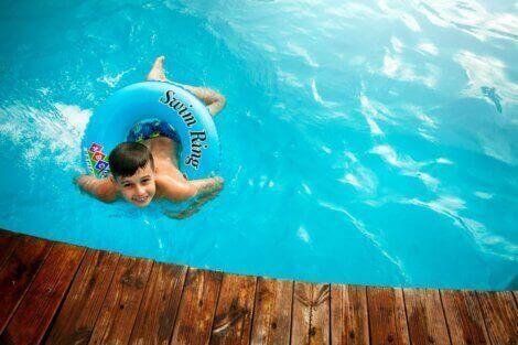 dreng svømmer i pool i haven