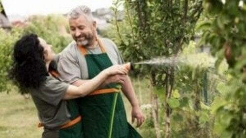Mand og kvinde vander planter i haven