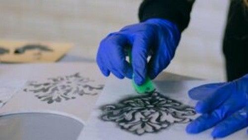 Person bruger skabelon og svamp til kreativt projekt