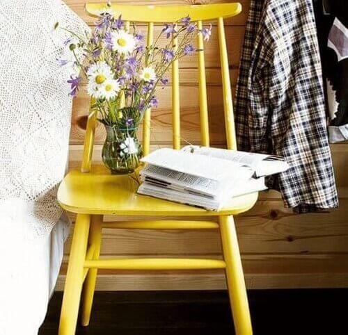 Gul stol brugt som bord ved sengen