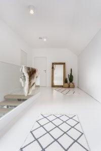 Langer weißer Flur mit weißem Teppich