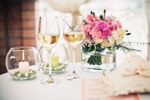 Blumenstraß in einer Vase neben zwei Weingläsern