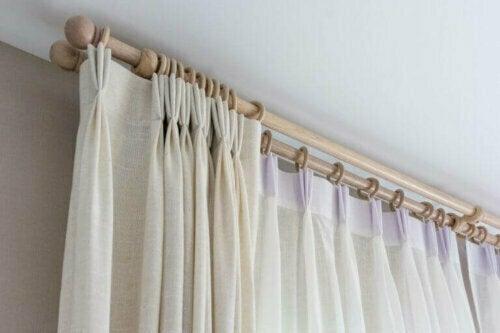 Eine Alternative zu Vorhangstangen sind Schienen, die du hinter einem Gesims versteckst und die den Raum größer wirken lassen können.