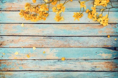 Abgenutztes Holz und gelbe Blumen