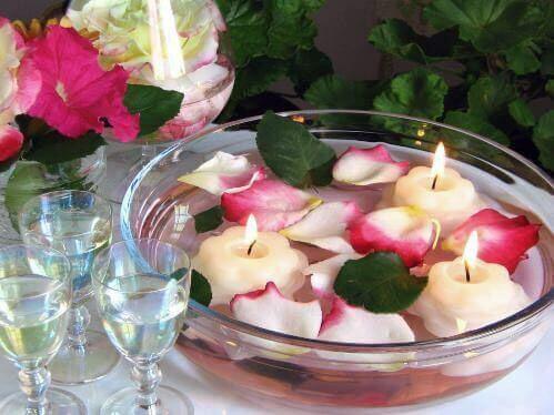 Arrangement aus schwimmenden Blütenblättern und schwimmenden Kerzen