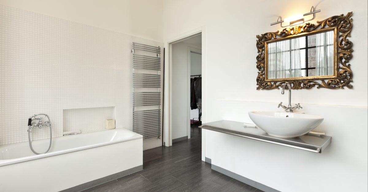 Baño en blanco con detalle espejo en dorado