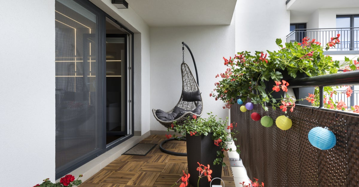 Balcón decorado con farolillos de colores, plantas y una hamaca