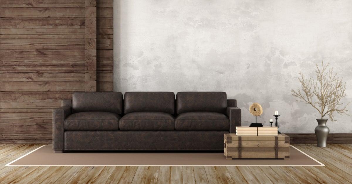 Salón rústico con sofá de piel oscuro y pared y suelo de madera