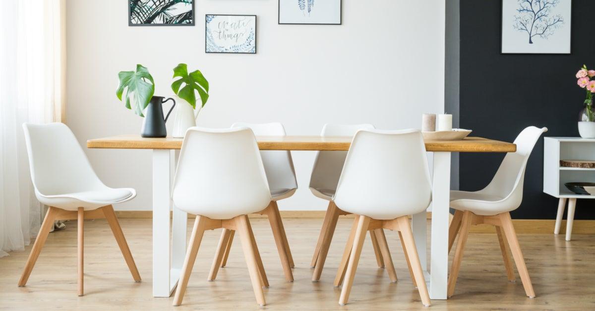 Sillas de comedor entorno a la mesa de color blanco y patas de madera